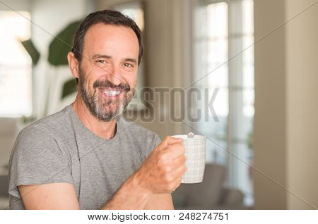 Middle age man drinking coffee in a cup with a happy face standing and smiling with a confident smile showing teeth