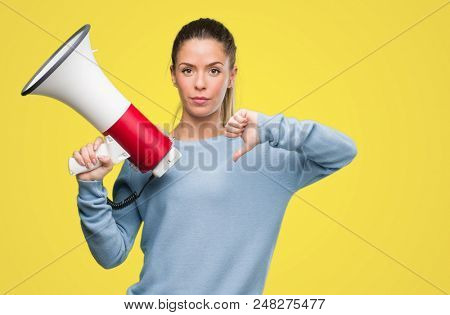 Beautiful young woman holding megaphone with angry face, negative sign showing dislike with thumbs down, rejection concept poster