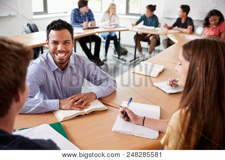 Male High School Tutor With Pupils Sitting At Table Teaching Maths Class