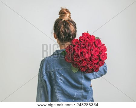 Back View Of Young Woman In Denim Jacket Holding Bunch Of Red Roses On Shoulder. Girl With Bun Updo