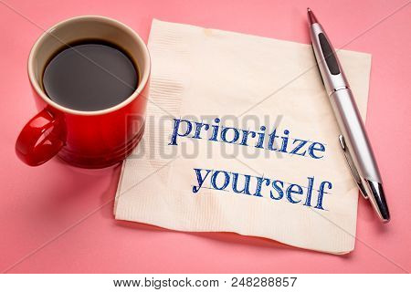 prioritize yourself advice - handwriting on a napkin with a cup of espresso coffee poster