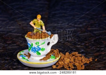 A Tiny Miniature Male Worker Figure Shoveling Coffee Grains Out Of A Miniature Tea Cup And Saucer