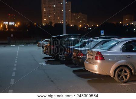 Cars At Night In Parking Lot Under Lantern