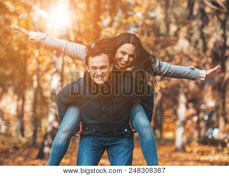 Young Happy Couple Have Fun In Park In Autumn. Happy Time Spending Outdoor Concept. Young Family Hav