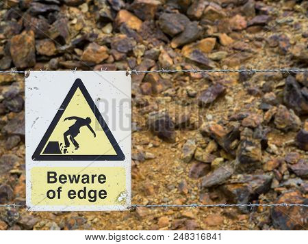 Warning Sign At The Edge Of An Unstable Cliff Edge