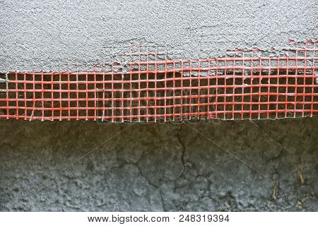 Texture Of A Red Plastic Mesh On A Gray Concrete Wall