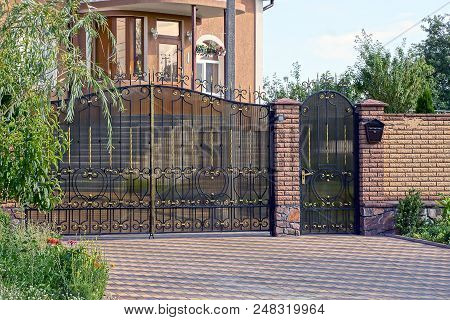 A Large Metal Gate And A Brown Brick Fence In The Street