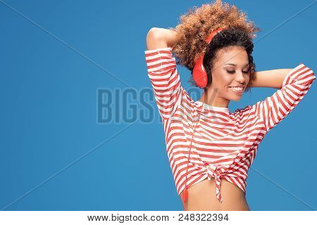 Adorable Happy Afro Girl With Red Headphones Smiling.