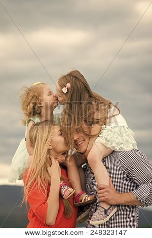 Family Day. Girls Kiss On Mother Father Shoulders On Cloudy Sky. Happy Childhood, Family, Love. Moth