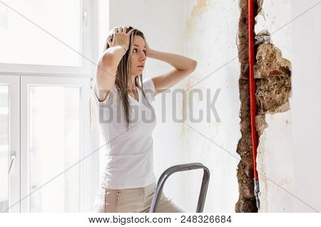 Woman Looking At Damage After A Water Pipe Leak