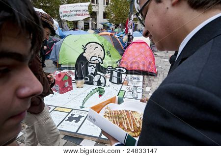 LONDON, UK -OCTOBER 31:Ironic view of an office worker having his lunch while admiring a begging banker sculpture donated to protesters by Banksy on October 31, 2011 in London.