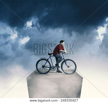 Biker On A Long Cube High In The Clouds.