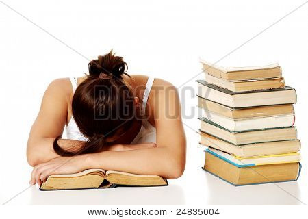 Young pretty girl sleeping on the desk with her head on the book  near the pile of books.
