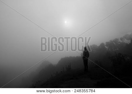 Black And White Photo Of Man Standing On The Peak Of Sandstone. Misty Valley. Foggy Mountains. Sun I
