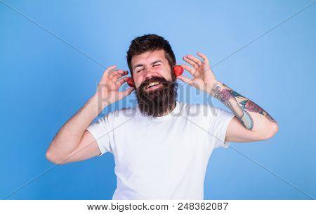 Man Bearded Hipster Red Ripe Strawberry Ears As Headphones. Summer Hit Concept. Hipster Beard Listen