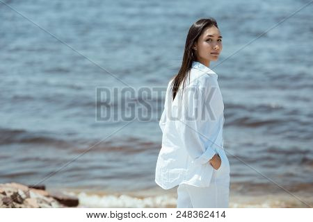 Attractive Asian Woman With Hands In Pockets Looking At Camera By Sea