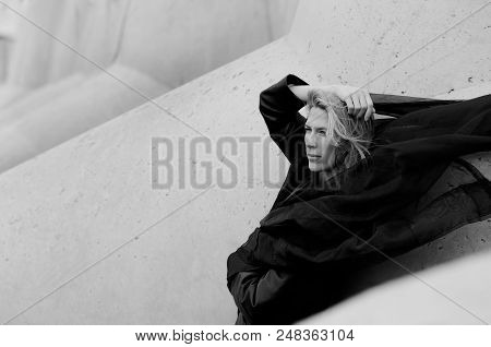 Beautiful Woman Portrait, Flying Black Scarf And Blonde Long Hair, Concrete Blocks Background In Sea