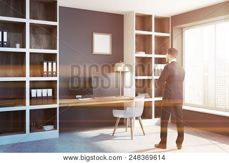 Businessman In A Panoramic Window Gray Home Office Interior With A Concrete Floor, A Computer Table