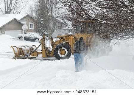 Chanhassen, Mn - April 14, 2018: City Worker And Homeowner Clearing Snow During April Mn Blizzard. T