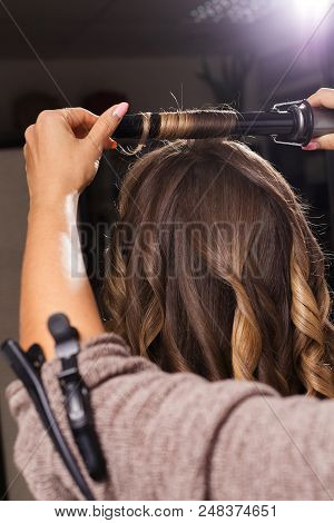 professional hairdresser making a hair curling to a model with long hair in a beauty salon. hairgrip is pinned on a sleeve of a woman. concept of stylist training poster