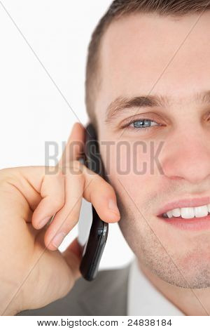 Close up of a young businessman making a phone call against a white background
