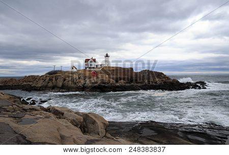 Cape Neddick Lighthouse Stands On Nubble Island With Waves Crashing On Rocky Shore