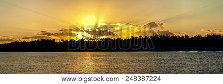 A Spectacular Panoramic Golden Colored Cloudy Sunrise Seascape Featuring Bold Crepuscular Rays (sun