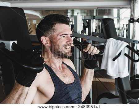 Stylish, Muscular Man In Black Training Gloves And Short Sports Shirt, Performs Strength Exercises O