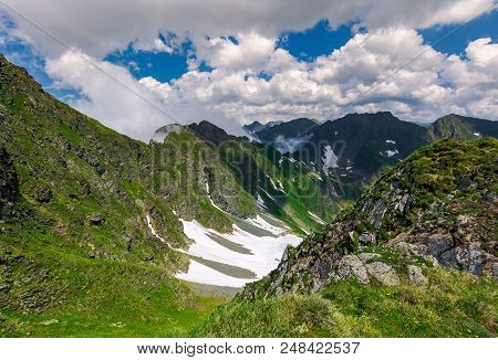 Cliffs In The Valley Of Fagaras Mountains. Lovely Summer Scenery On A Cloudy Day. Spots Of Snow On G
