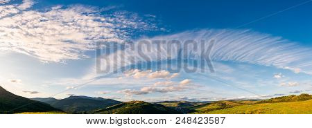 Gorgeous Evening Clouds Over The Mountains. Lovely Panorama Of Striking Cloudscape On A Blue Sky