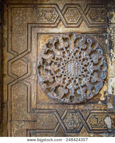 Round Floral Patterns Framed By Geometrical Patterns Carved Into The Exterior Ancient Stone Wall Of