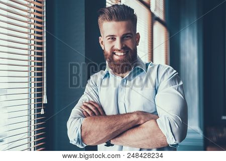 Young And Handsome Businessman In White Shirt Near Windows In Modern Office. Bearded Young Man Near
