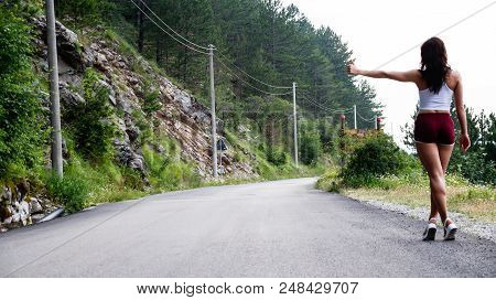 Sexy Girl Stands On Hitchhiking In Short Red Shorts And A White T-shirt.