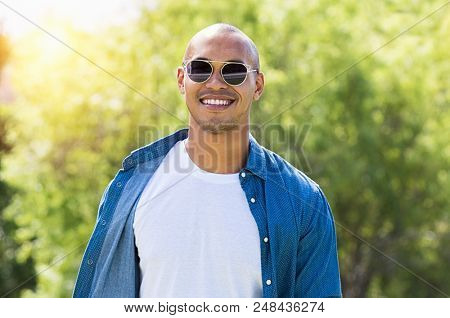 Portrait of smiling african man looking at camera with sunglasses. Happy guy enjoying the summer outdoor. Cheerful young man wearing white tshirt and blue shirt at park.