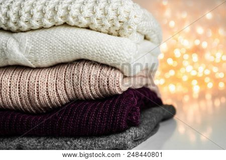 Warm knitted sweaters. Pile of knitted clothes on warm background, sweaters, knitwear, space for text, Autumn winter concept. poster