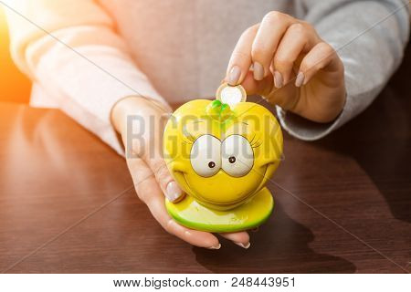 Woman Putting Coins In A Funny Yellow Moneybox In Rays Of The Sun. Concept Of Future, Business, Savi