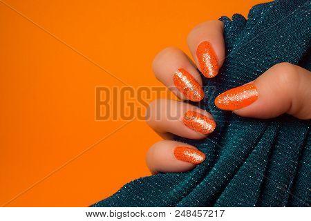 Female Hand With Glittered Orange Nails Is Holding Turquoise Textile On Orange Background, Manicure