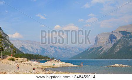 Banff, Ab / Canada - July 28, 2017:  Visitors Enjoy The Beach Of Lake Minnewanka, A Glacial Lake Pop