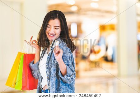 Happy Beautiful Asian Woman Smile At Credit Card, Hold Shopping Bags, Copy Space On Shopping Mall Ba