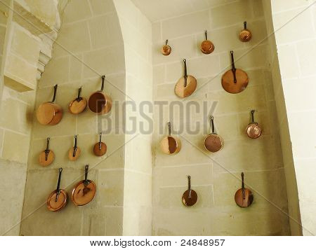 Copper pans on the wall of a medieval kitchen