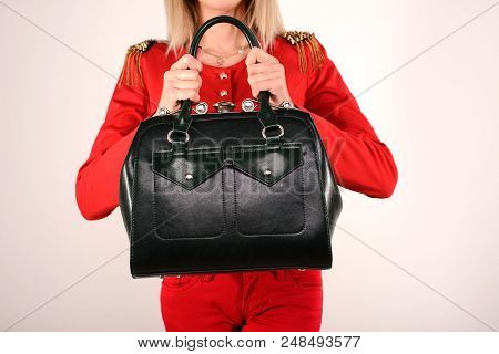 Slender Girl In A Red Suit Holds In Hands Green Bag Stands