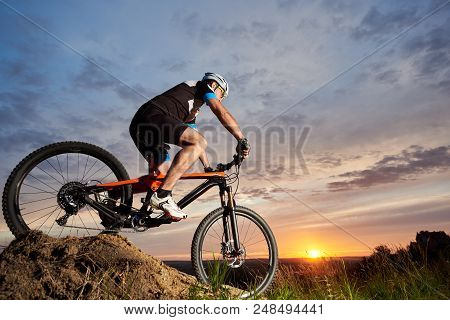 Active Male Cyclist Wearing Sportswear And Helmet, Riding Bicycle Alone And Rolling Down Hill. Sport