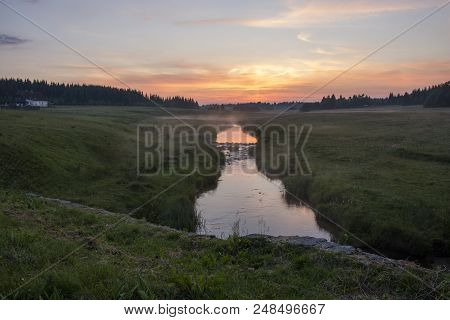 A Brook Flowing Through The Mountain Landscape. Fog Above The Brook. Sunset Sky And Colorful Clouds
