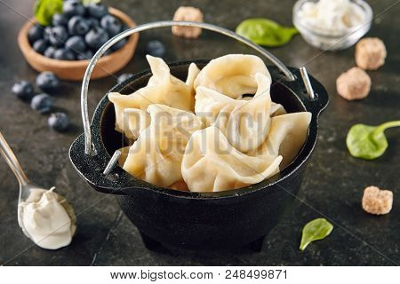 Dumplings with Blueberries. Berriesjiaozi, Dimsum, Momo or Ha Gao on Dark Background. Asian Food of Dough Based on Flour Stuffed with Meat, Fish, Vegetables, or Sweets