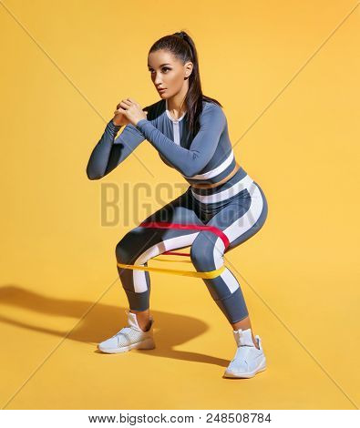 Sporty Woman Squatting Doing Sit-ups With Resistance Band. Photo Of Latin Woman In Fashionable Sport