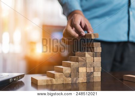 Hand Of Businessman Pulling Wooden Block Before Fail On Building Tower At Home And Drape Change, Cho