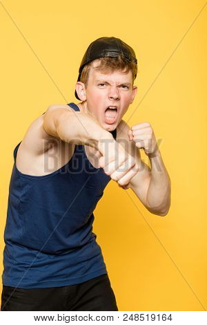 Cocky Arrogant Fighter. Street Thug And Hooligan. Man Punching A Fist. Portrait Of A Young Guy On Ye