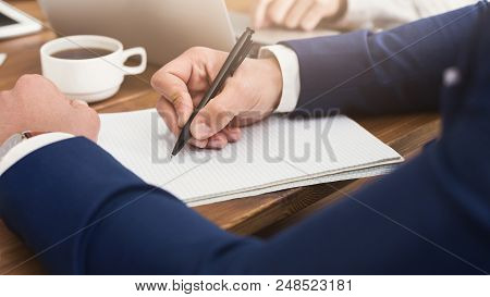 Male Hand Holding Pen Ready To Make Note In Notebook. Businessman In Suit Writing Thoughts At Person