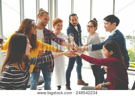 Multiethnic Young Team Stack Hands Together As Unity And Teamwork In Modern Office. Diverse Group To