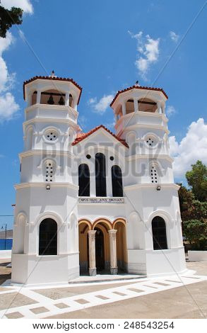 Signage saying church of Agios Nikolaos (Saint Nicholas) on the seafront church at Livadia on the Greek island of Tilos. St. Nicholas is the patron saint of fishermen.
